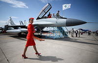 An Aeroflot flight attendant walks by a Mikoyan MiG 29K fighter jet
