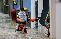 A French firefighter carries a child during rescue operations in the middle of submerged streets due to heavy rain falls and violent storm that hit Aude department overnight in Trebes, France