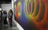 "People walk past a painting by Julio Le Parc titled ""Alchimie 396"" displayed at the Nara Roesler Gallery at Art Basel, Miami Beach"
