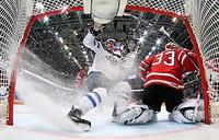 Игрок сборной Финляндии Томми Кивисте и вратарь сборной Канады Кэм Тальбо