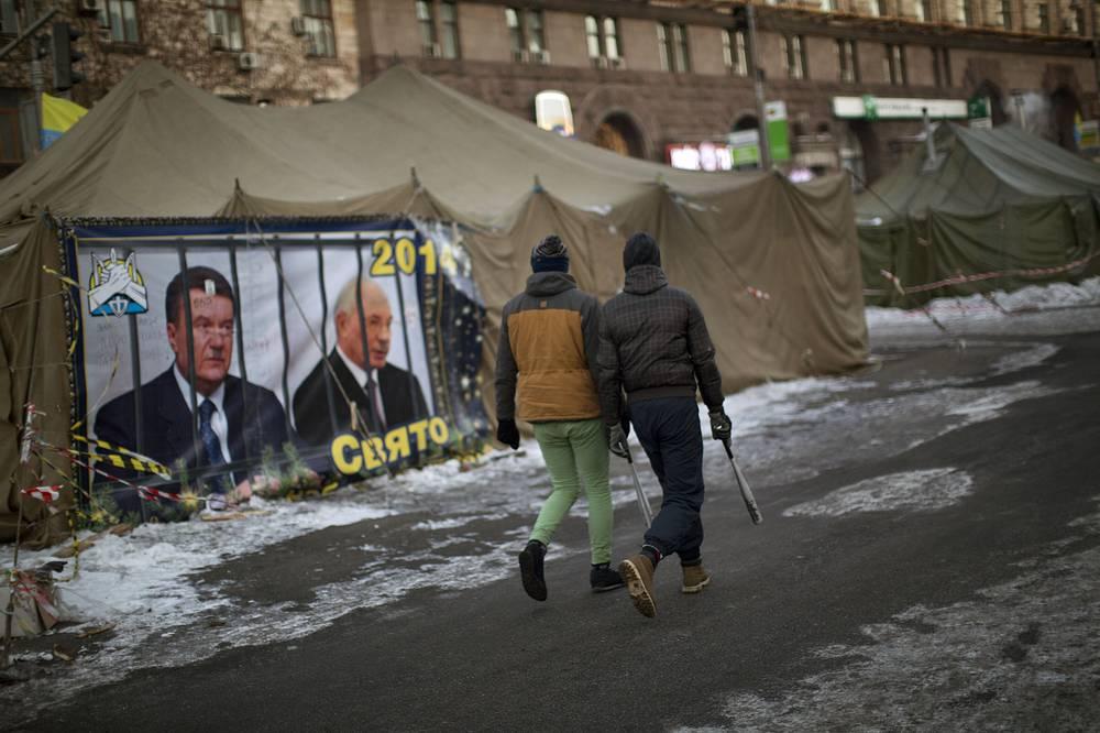 Opposition supporters carrying baseball sticks walk past a poster where Ukrainian President Viktor Yanukovych (R) and former PM Mykola Azarov (R) are seen behind bars