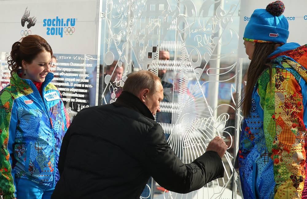 Figure skater Irina Slutskaya, Russia;s president Vladimir Putin, and coastal Olympic village mayor, pole vaulter Yelena Isinbayeva (L-R) visiting the Olympic village in the coastal cluster