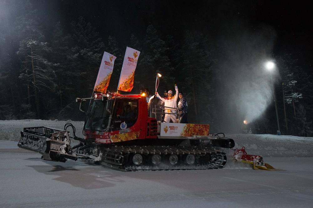 Torch bearer Evgeny Nefedov holding an Olympic torch, rides on a snowplough during the Olympic torch relay in the Siberian city of Divnogorsk