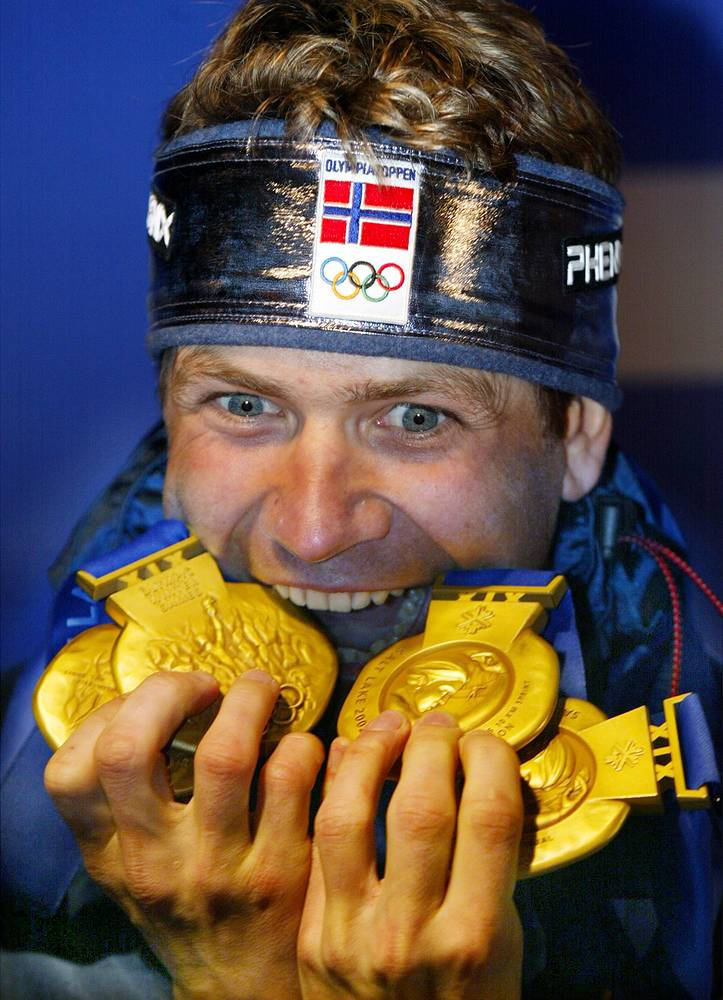 Norway's Ole Einar Bjoerndalen bites four gold medals he won in the 2002 Winter Olympic Games in Salt Lake City, 2002