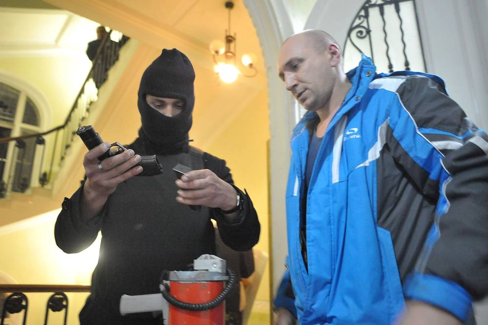 A protester examines a pistol in the seized regional Interior Ministry department in the west-Ukrainian city of Lviv