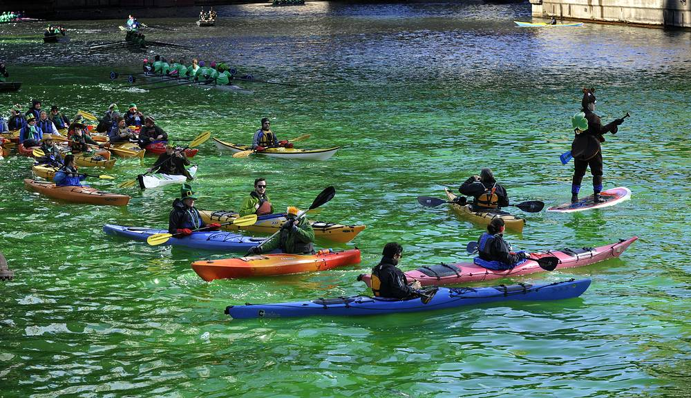Kayakers float on the Chicago River after it was dyed green ahead of the St. Patrick's Day parade in Chicago, USA