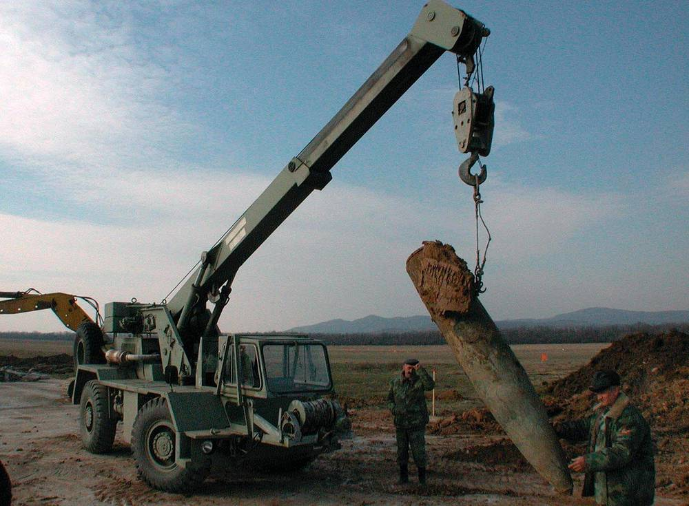 Defusing forces use a crane to lift a unexploded bomb weighing 1,000 kg on a vehicle at the Nis airport in 2003