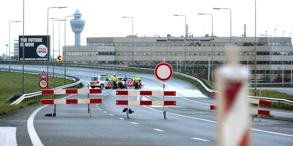 Barriers and police vehicles are seen on an exit of the Dutch highway A5 to Schiphol airport