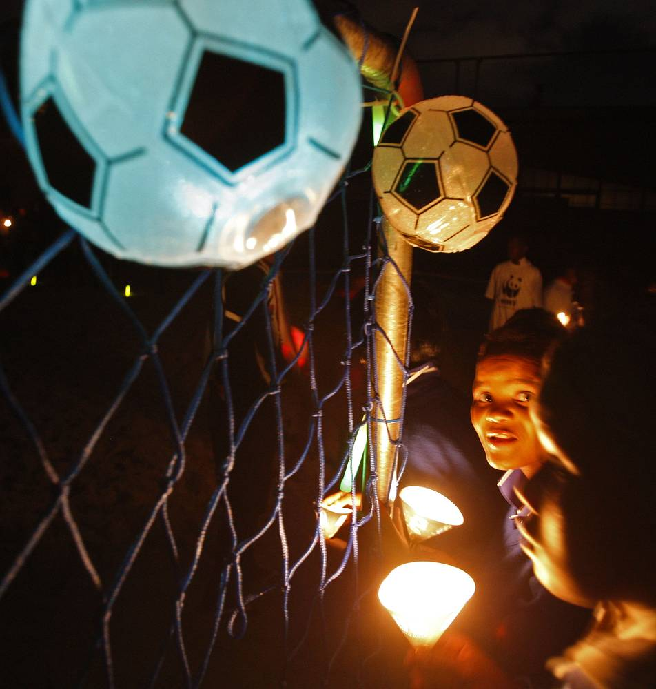 People look on holding candle lights as other play soccer, at a beach outside Cape Town, south Africa, 2010