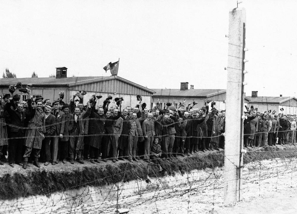 The first concentration camp in Germany, Dachau, was founded in March 1933. Photo: prisoners at the electric fence of Dachau concentration camp greeting Allied troops