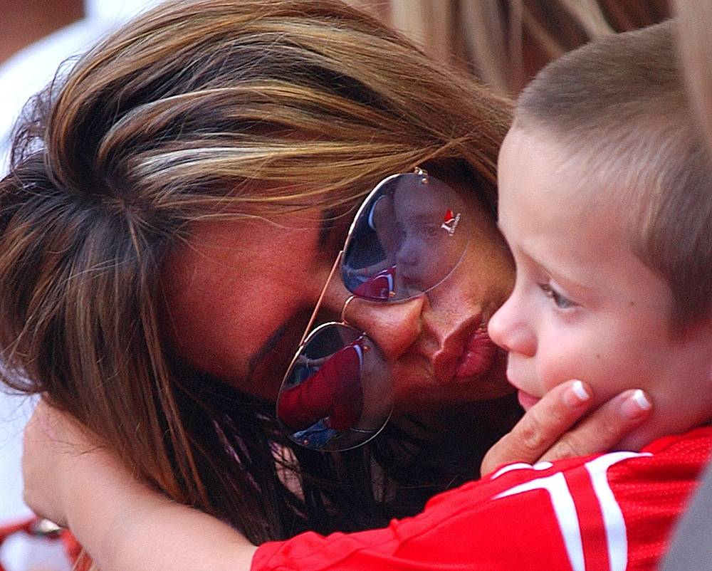 The couple has four children. Photo: Victoria with her son at a stadium