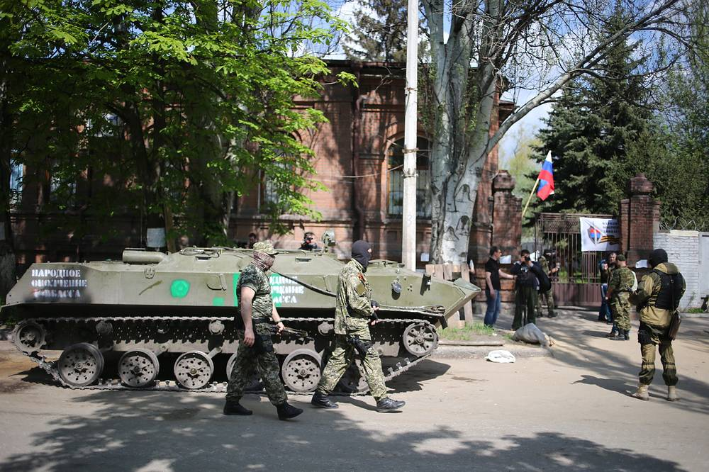 Members of self defense units and an armoured vehicle outside the Ukraine Security Service building in Sloviansk