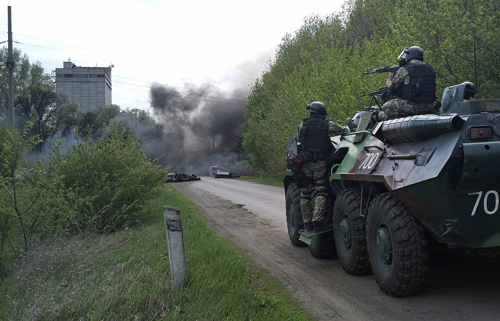 Ukrainian troops take position next to burning tires at a pro Russian checkpoint following an attack by Ukrainian troops outside in Sloviansk