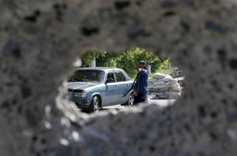 An armed man checks a car at the barricades on a road leading into Sloviansk