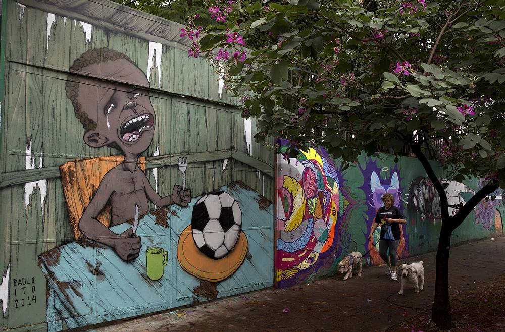 A mural by Brazilian street artist Paulo Ito shows a hungry child who is served a soccer ball