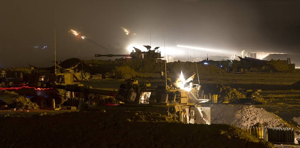 Israeli 155mm artillery canons fire from a base in southern Israel into the Gaza Strip