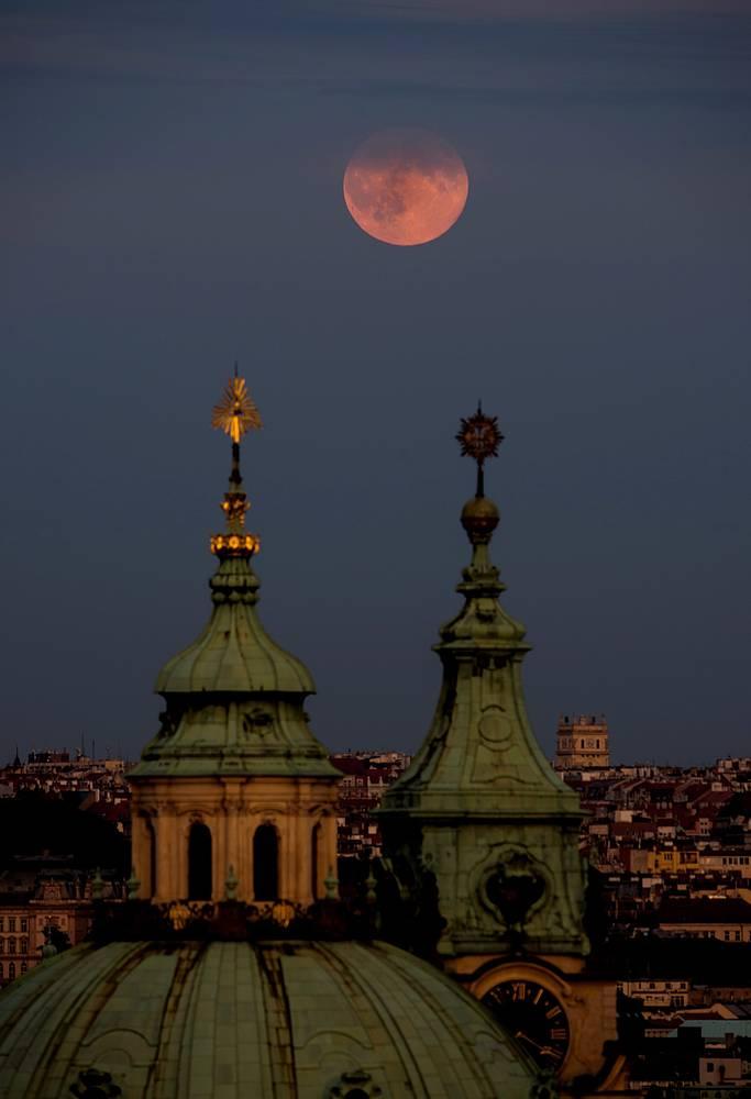 Supermoon rises over the St Nicholas Church in central Prague, Czech Republic