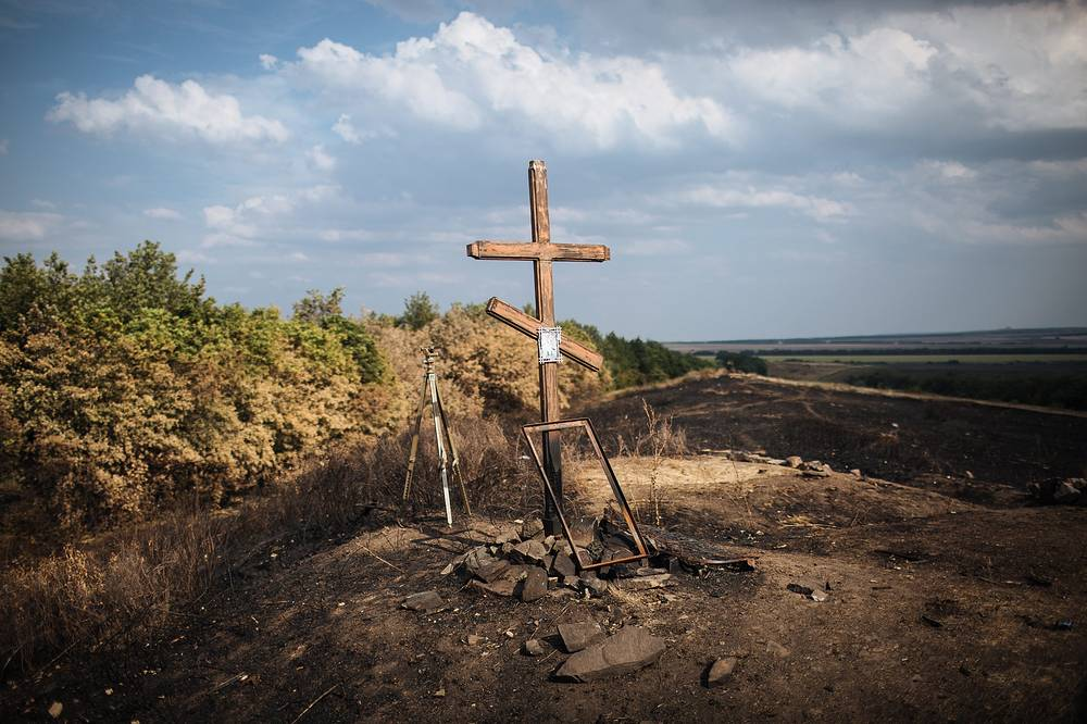 A cross is placed on a burnt out field in Ukraine's Donetsk Region