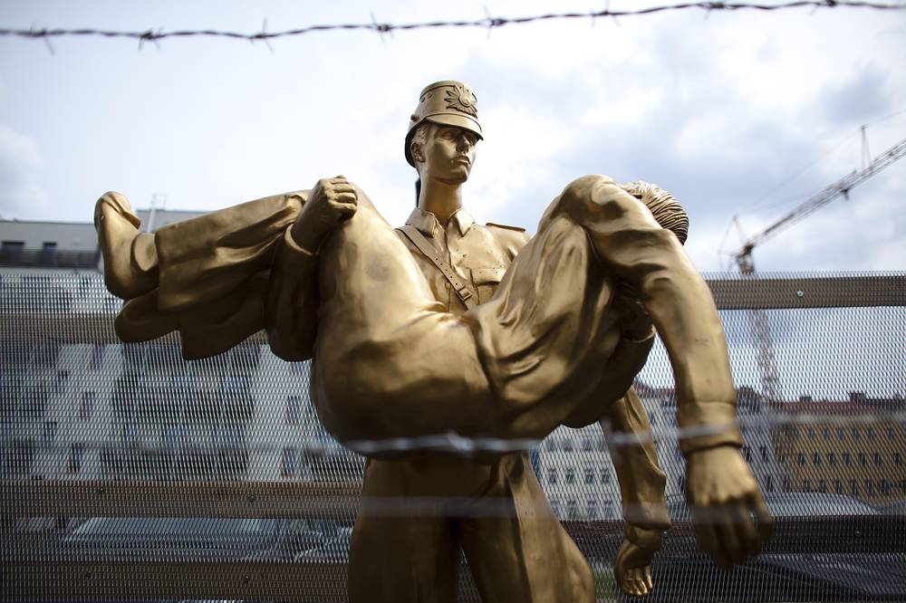 Photo: A sculpture at Bernauer Strasse in Berlin. The artwork shows a scene from August 17, 1962 when dying Peter Fechter was carried away by East German border guards who shot him down when he tried to cross the Berlin wall and became the first person who was killed there