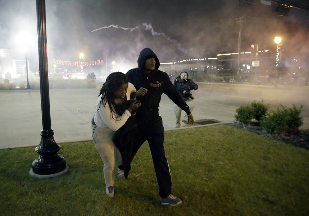 Photo: Protesters run for shelter as smoke fills the streets after the announcement of the grand jury decision in Ferguson