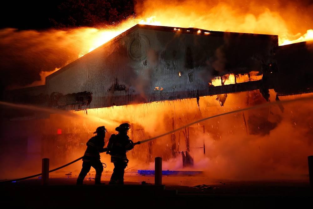 Photo: Firefighters work on extinguishing the burning restaurant in Ferguson