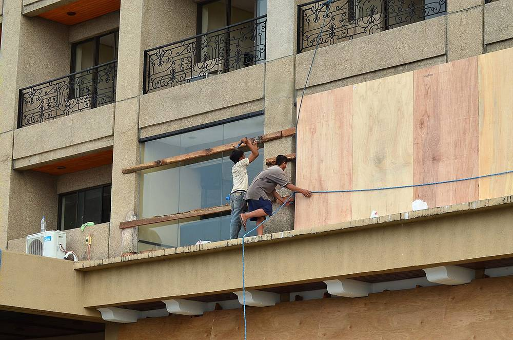 Photo: Workers reinforce a building ahead of evacuation in Ormoc City, Philippines, 05 December 2014