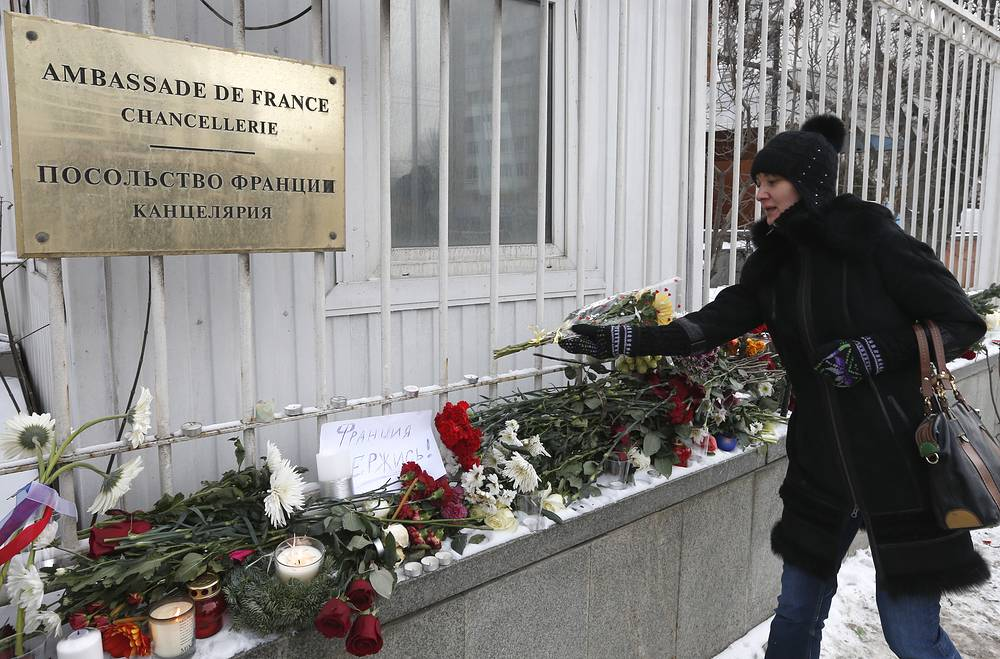 Woman lays flowers near French embassy in Moscow, Russia