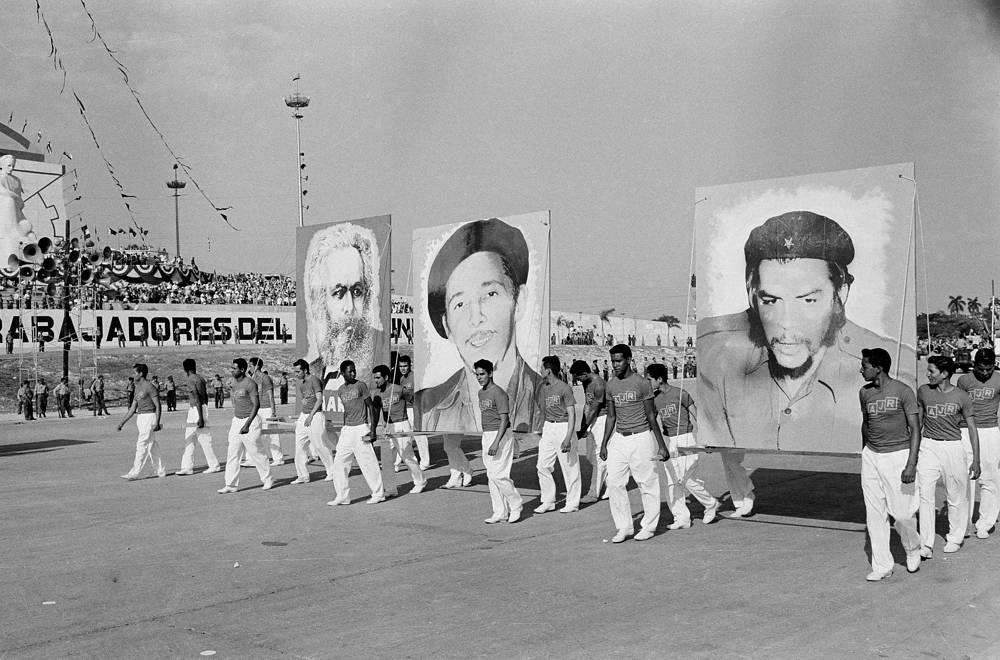 "On April 16 Fidel Castro officially declared the socialist nature of Cuban Revolution. Photo: Cuban athletes carrying portraits of Karl Marx, Raul Castro, and Ernest ""Che"" Guevara, during May Day parade in Havana, May 1, 1961"