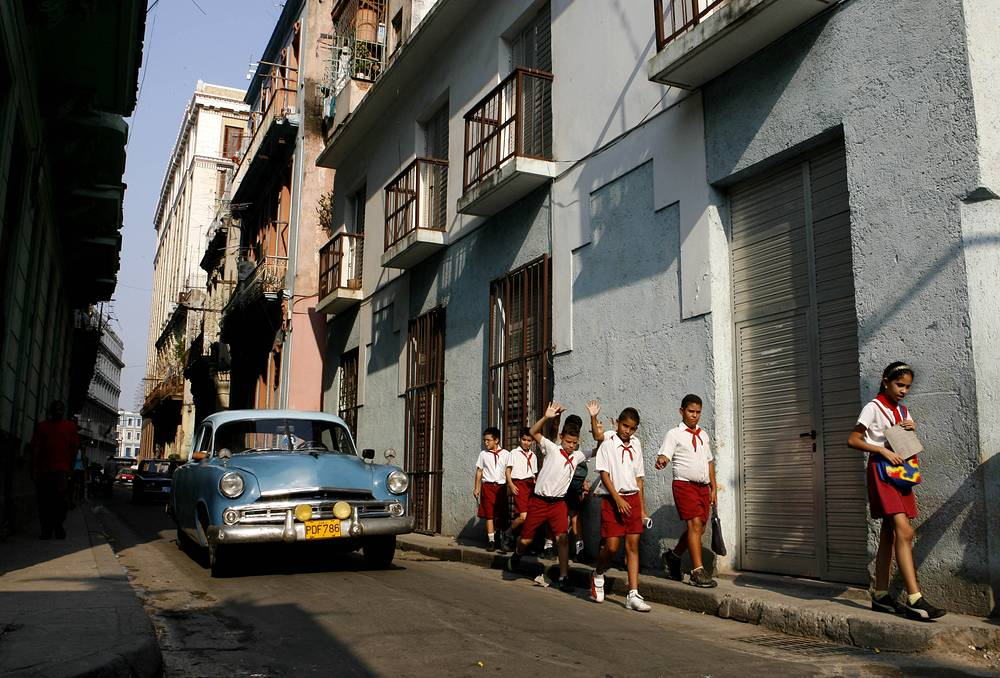 Photo: A classic car is seen as Cuban students make their way down a street  in San Juan de Dios  in Old Havana, Cuba, 2006