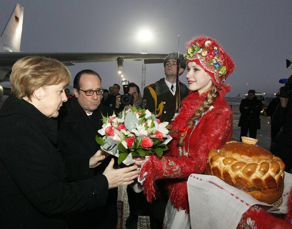 German Chancellor Angela Merkel and French President Francois Hollande during a welcoming ceremony at an airport near Minsk, Belarus