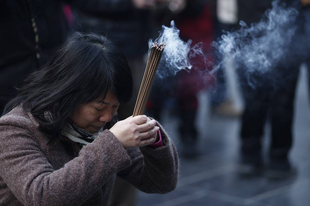 Buddhist devotees burning incense sticks during prayers at the Yonghegong Lama Temple to mark the first day of the Lunar New Year in Beijing, China