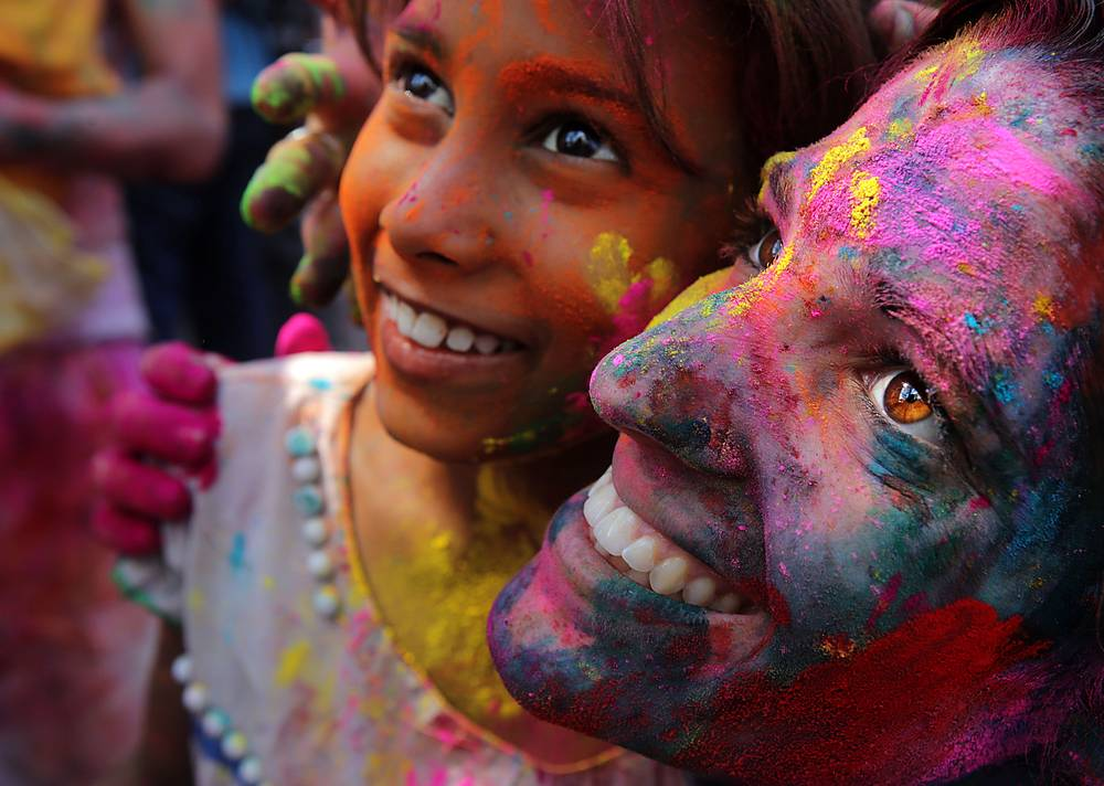 Local people and foreign tourists applying color on each other as they celebrate the Holi festival in Calcutta, India