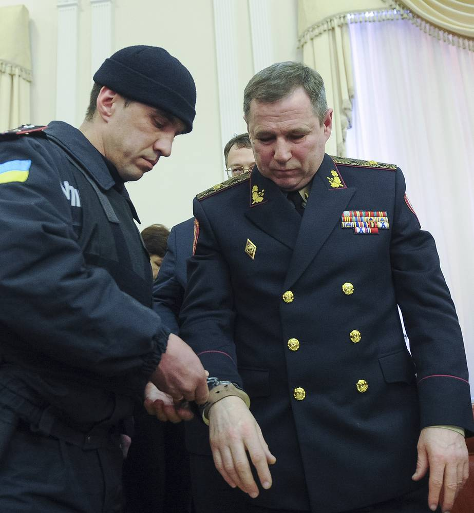 A policeman handcuffs the first deputy of the head of Ukraine's state service for emergency situations