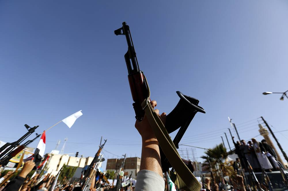 Houthi supporters raising their weapons while shouting anti-Saudi and US slogans during a demonstration in Sana'a