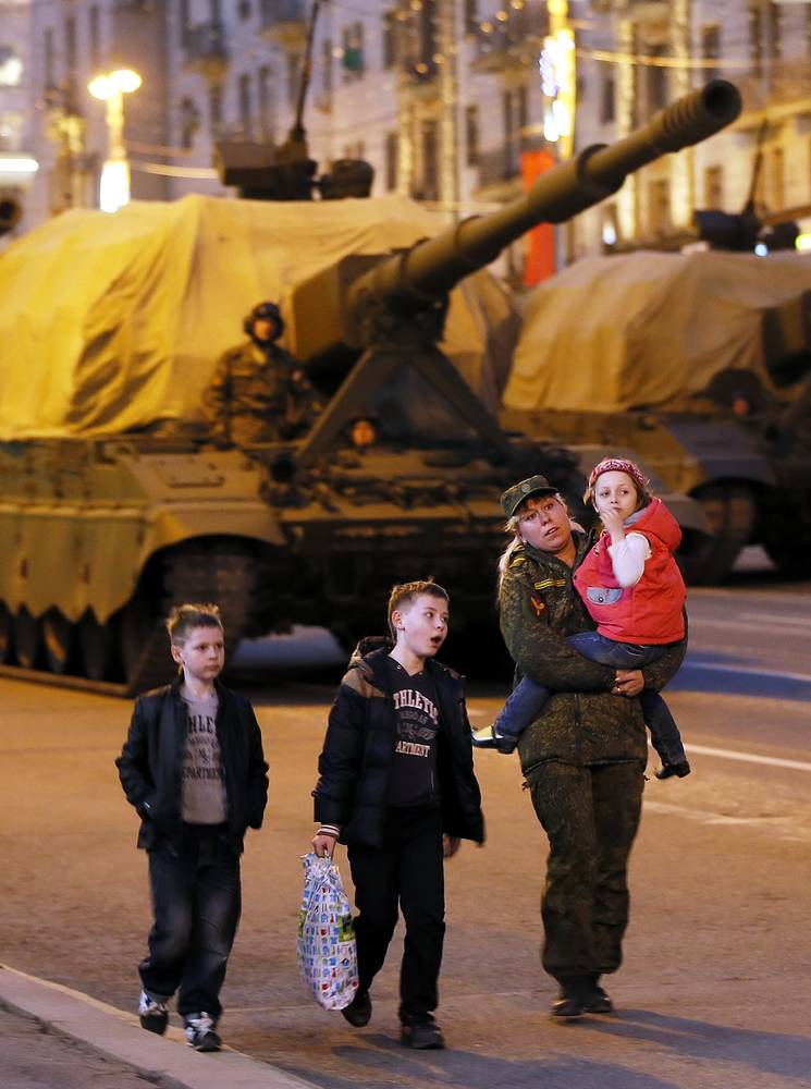 A woman in military uniform walks with her children past Russian self-propelled military hardware