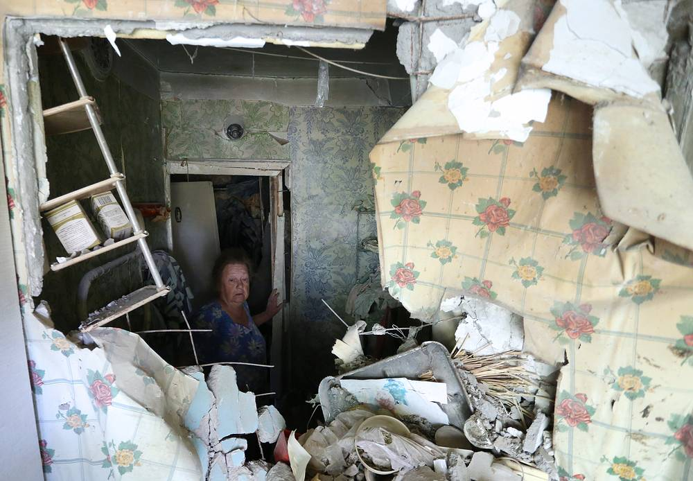 A local resident in an apartment damaged during a shelling attack on the village of Oktyabrsky, Kuibyshev District