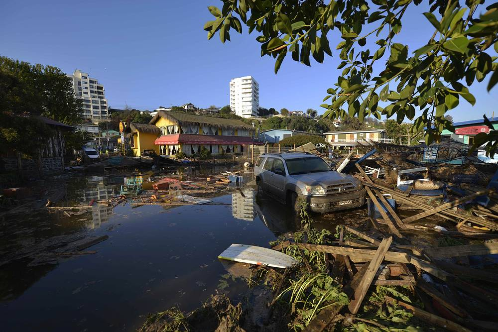 A car submerged in a flooded street after an earthquake-triggered tsunami in Concon, Chile