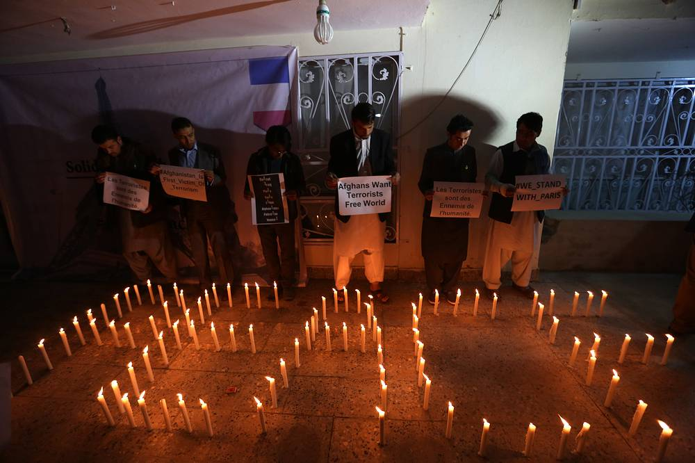 Candles spell out the word peace as Afghan youths and the Solidarity Party of Afghanistan hold a candlelight vigil for the victims of Paris terror attacks in Kabul, Afghanistan