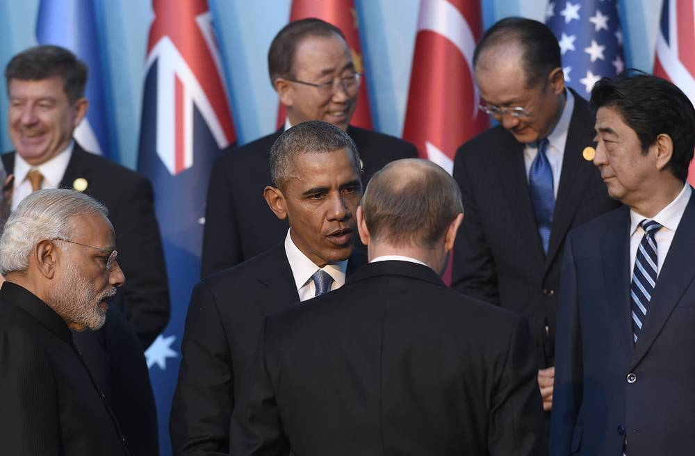 US President Barack Obama talking with Russia's President Vladimir Putin during a group photo with other leaders for the G20 Summit in Antalya