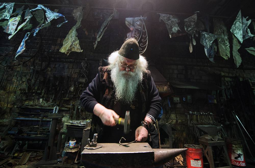 """Blacksmith Alexander Lysyakov minting a souvenir coin bearing an image of Russia's President Vladimir Putin and reading """"Everything will be alright"""", at his workshop, February 20, 2015"""
