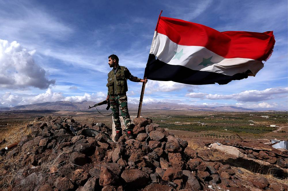 A Syrian government army soldier with a national flag, October 27, 2015