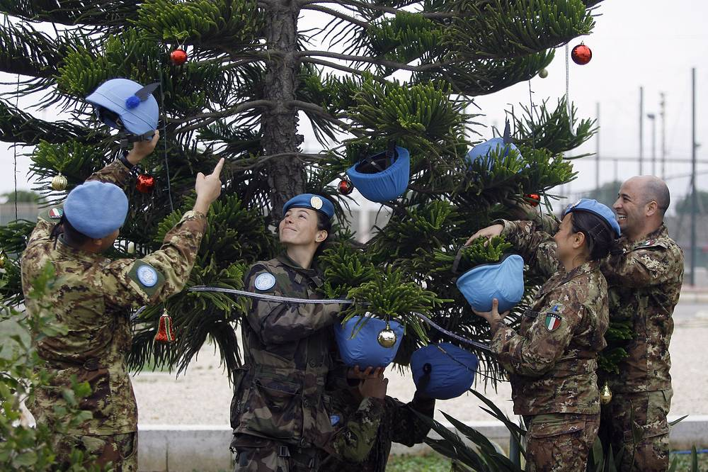 Italian UN peacekeepers decorating a Christmas tree with helmets at their base in the southern village of Chamaa, Lebanon