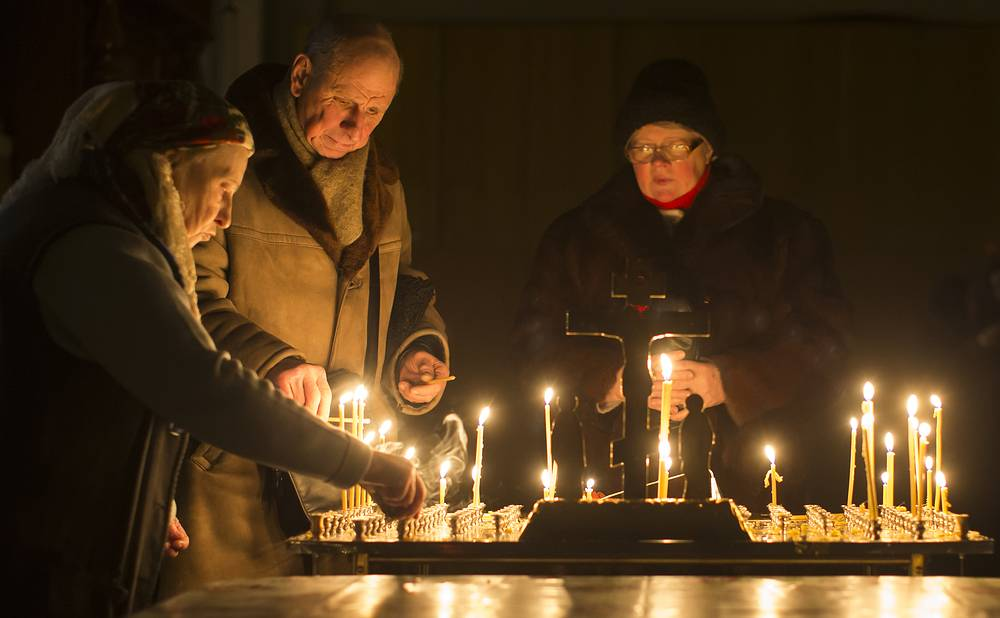 Lithuanian Orthodox believers lighting candles during the liturgy on Orthodox Christmas Eve in the Prechistensky, the Cathedral Palace in Vilnius, Lithuania