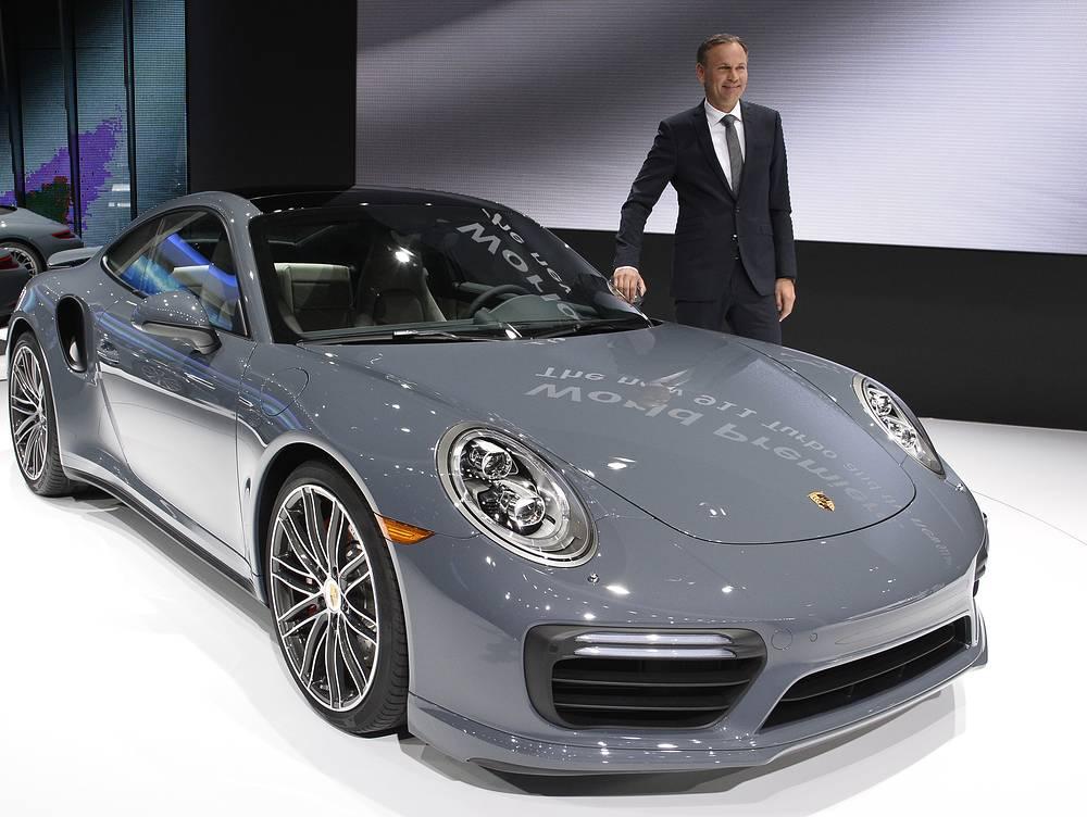 Oliver Blume CEO of Porsche standing next to the new Porsche 911 Turbo