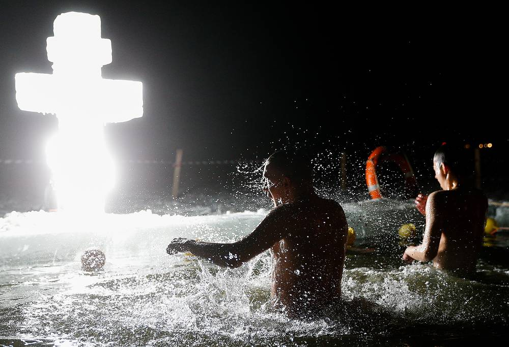 Believers plunging in the icy waters through a hole carved into a frozen river in Kaliningrad