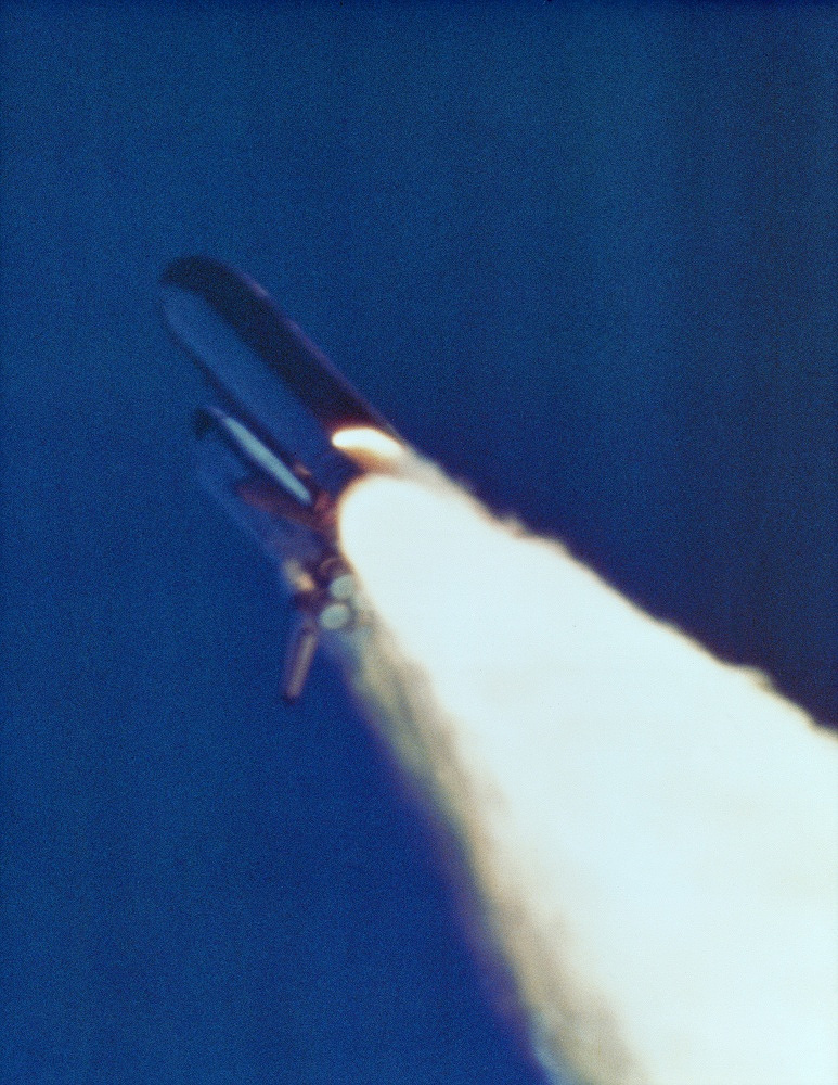 Unusual flame jutting from the side of a solid rocket booster on the space shuttle Challenger during its launch from the Kennedy Space Center in Cape Canaveral