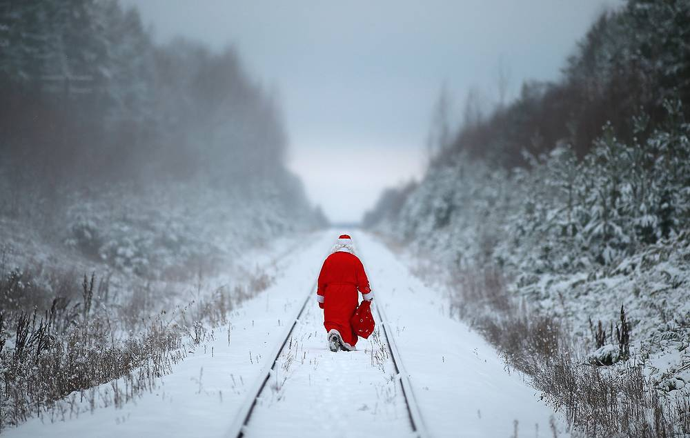 Father Frost (Russian Santa Claus) carrying a bag of presents in a forest, 2014