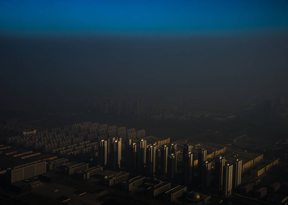 Chinese photographer Zhang Lei, for Tianjin Daily, 1st prize singles in the Contemporary Issues category. The picture shows a city in northern China shrouded in haze, Tianjin, China, 10 December 2015