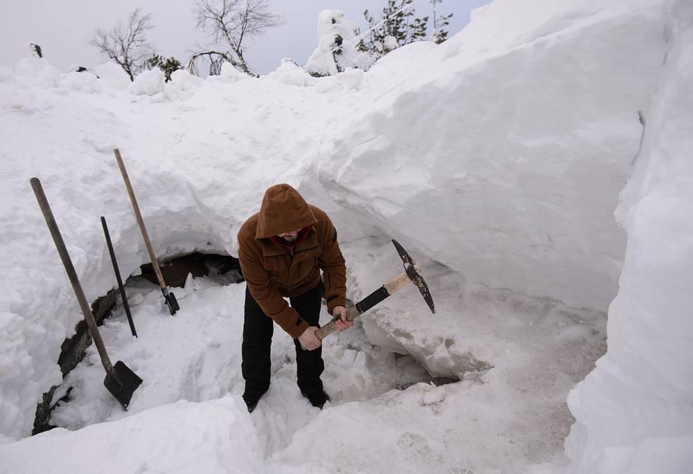 A Buddhist community member chops ice to get fresh water on Mount Kachkanar