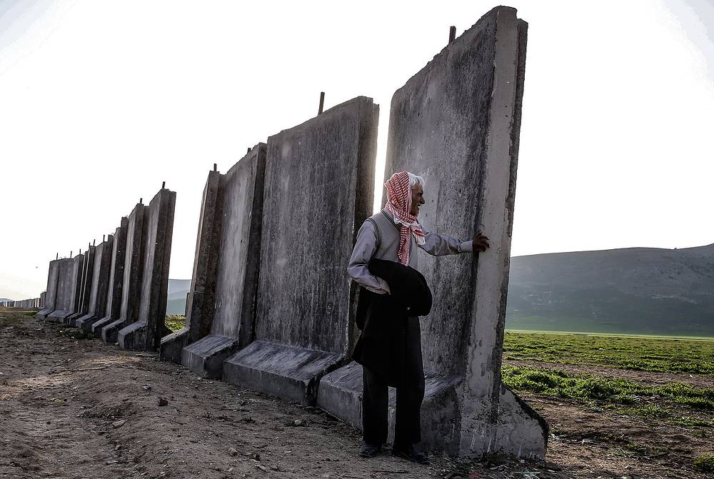Local man in a village by a wall that is being built along the Syrian-Turkish border